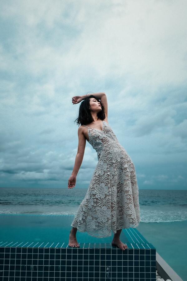Mulher na borda de uma piscina usando um vestido branco rendado com o mar no fundo
