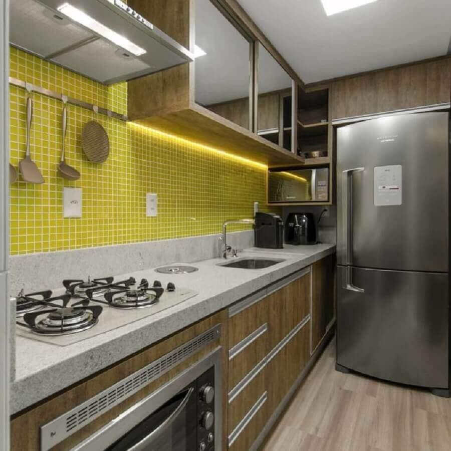 Cozinha moderna com armários de madeira, geladeira de inox, pastilhas amarelas na parede da pia e piso amadeirado.