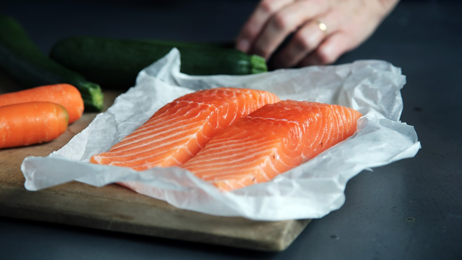 Salmon cut in half sitting on a cutting board next to vegetables.
