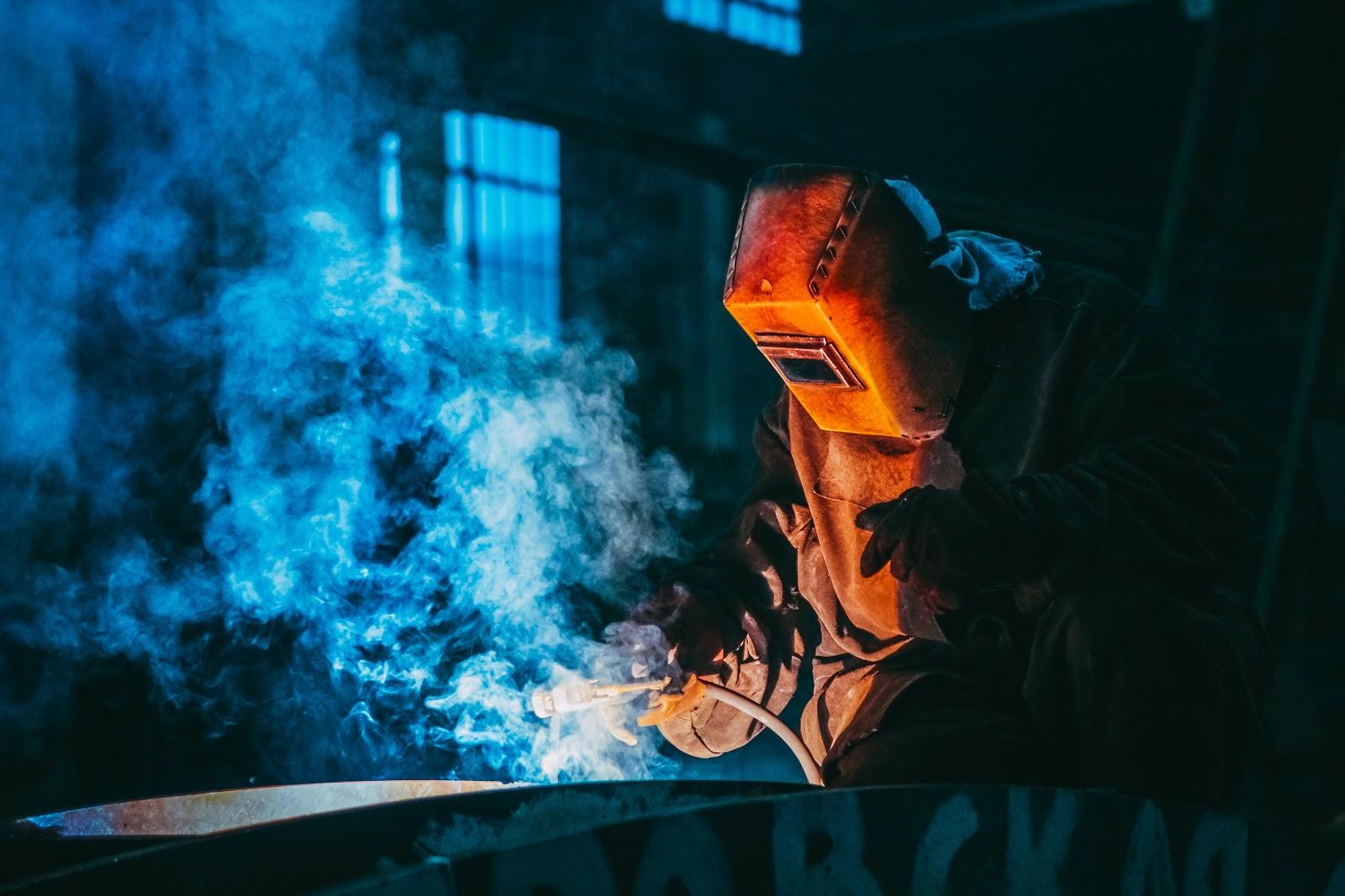 A welder works in a dark workshop.