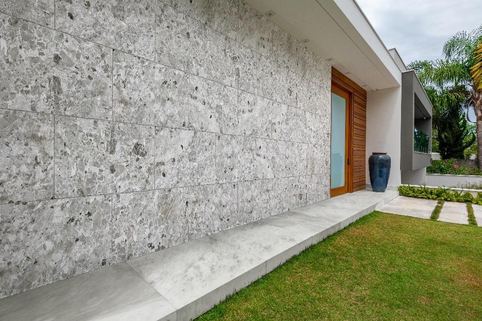 fachada de casa com revestimento de granilite em tom neutro nas paredes, gramado e porta grande de madeira.