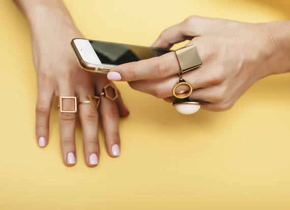 Woman wearing gold geometric jewelry holds iPhone