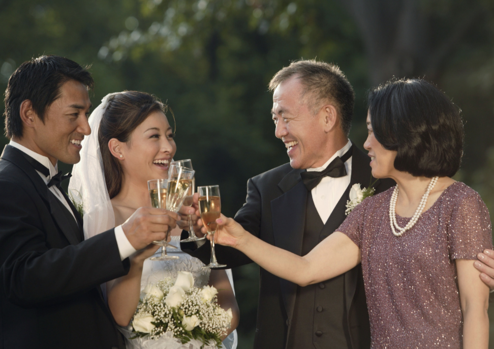 The father of the groom, mother of the groom or father of the bride and mother of the bride are toasting the couple with champagne.