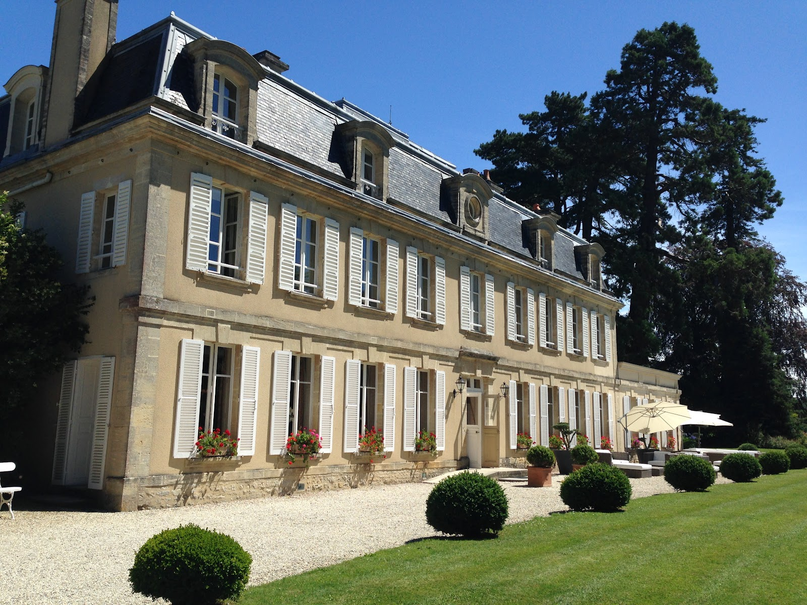 exterior chateau la cheneviere hotel located in a medieval castle. neatly cut lawn in foreground and trees in background, photographed on a sunny summer day in france