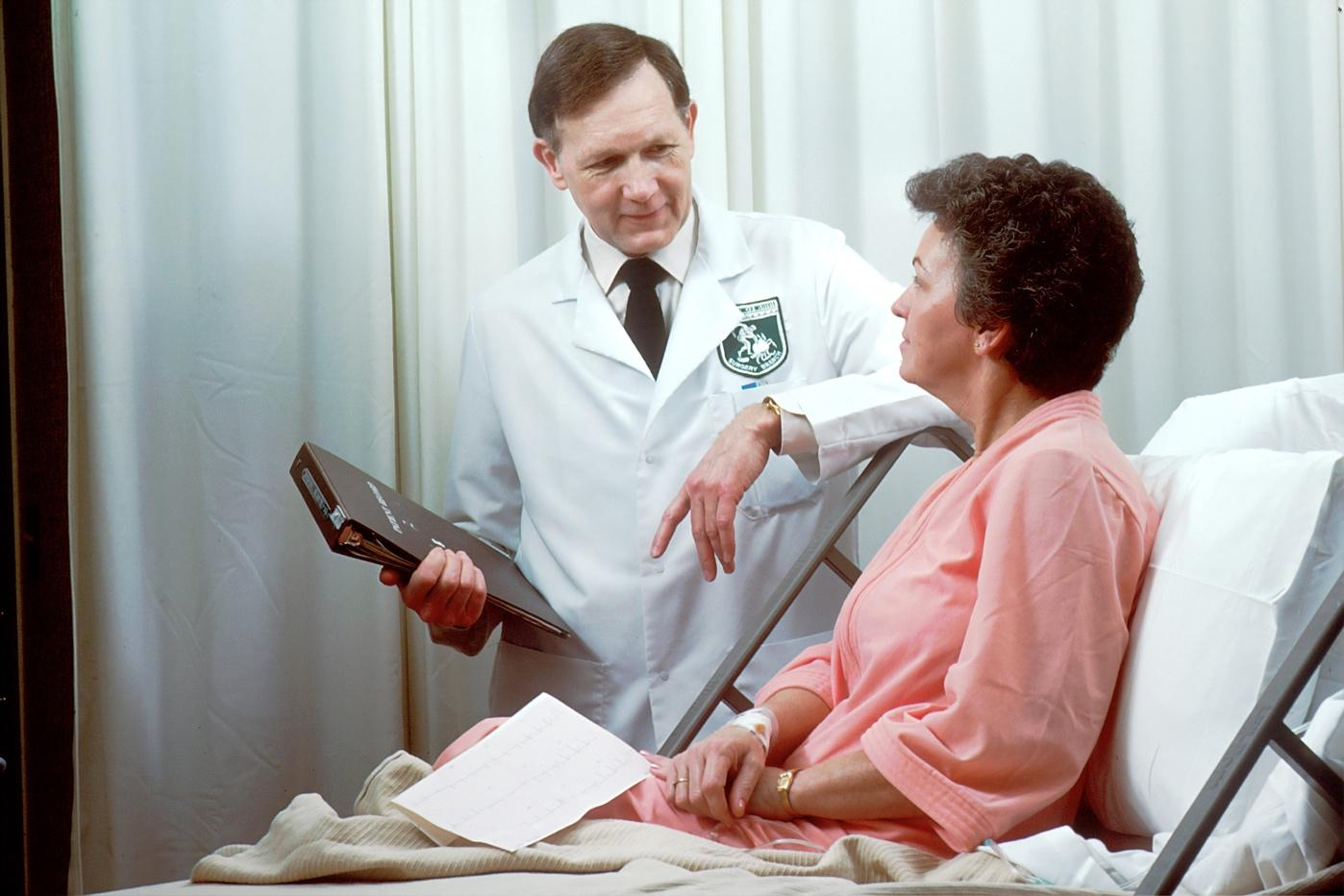 A doctor checking a patient's blood pressure  Description automatically generated with low confidence