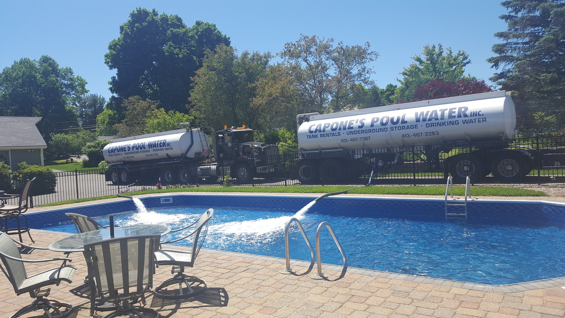 two pool water delivery trucks next to an inground pool filling it with water from their hoses