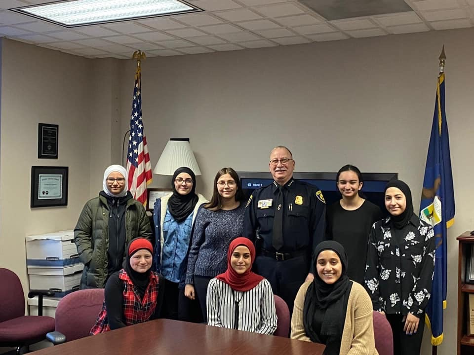 Three female students sitting at a table and five others standing with Chief Haddad in the Chief's office.