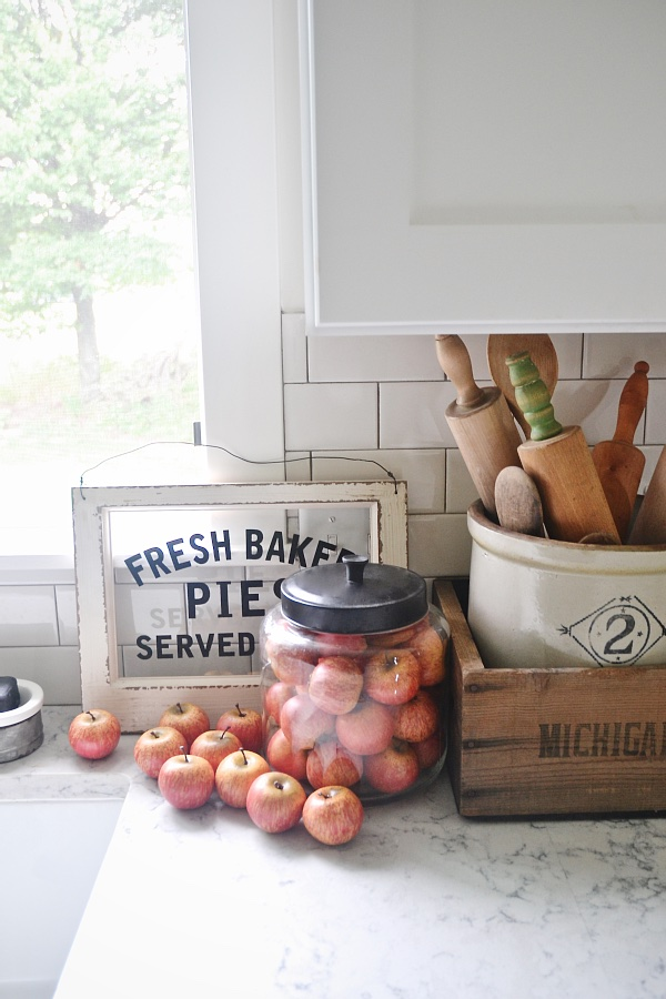 fall kitchen countertop decor with vintage apple pie sign, jar of apples, and large jar of utensils