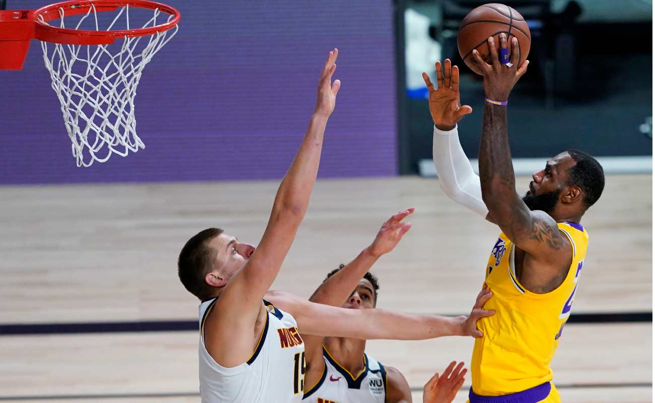 LeBron James of the Los Angeles Lakers shoots over Nikola Jokic and Michael Porter Jr. of the Denver Nuggets.