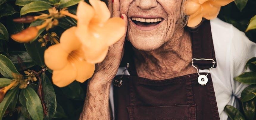 ID: La sonrisa de una señora mayor al lado de una flor amarilla.