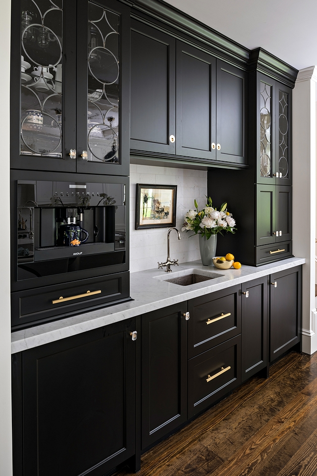black shaker cabinets with custom espresso bar, white countertops and dark wood floors