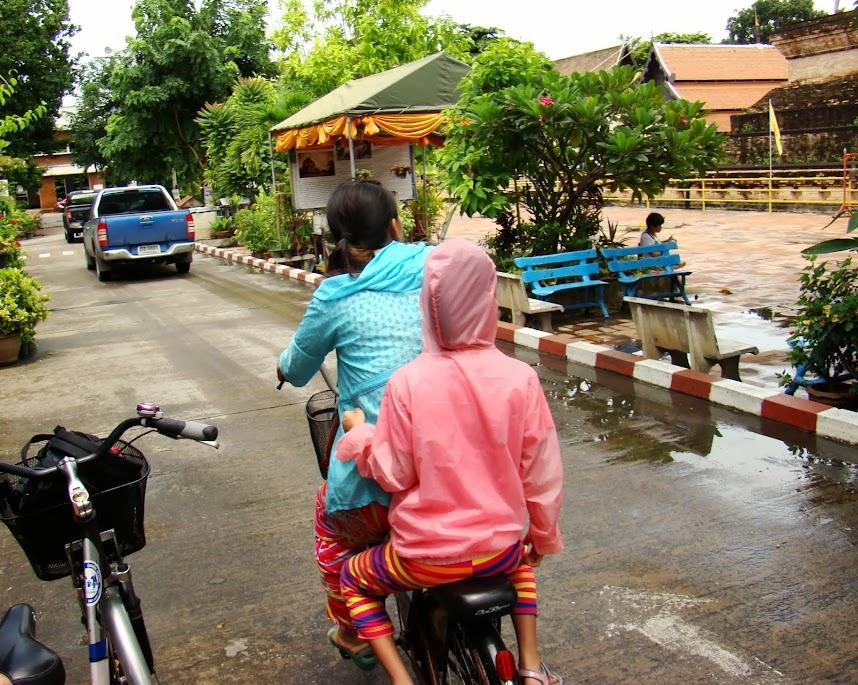 Niñas compartiendo bici en una calle del centro