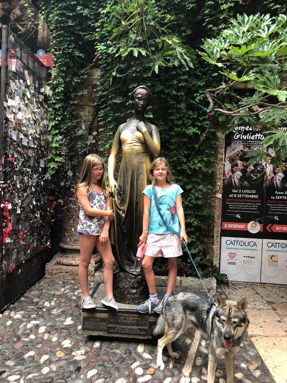zwei Mädchen stehen vor Statue und Hund liegt an der Leine davor