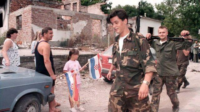 Хорватские беженцы, вернувшиеся в свои дома, приветствуют хорватских военных. 8 августа 1995 года