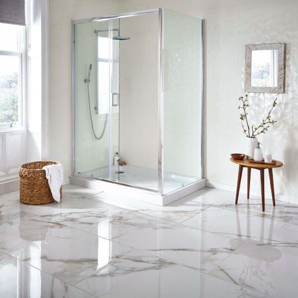 Banheiro com piso marmorizado branco, paredes brancas, box de vidro, banqueta de madeira e cesto de palha.
