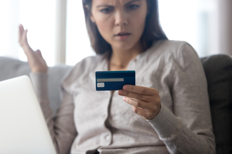 woman looking at credit card in disbelief