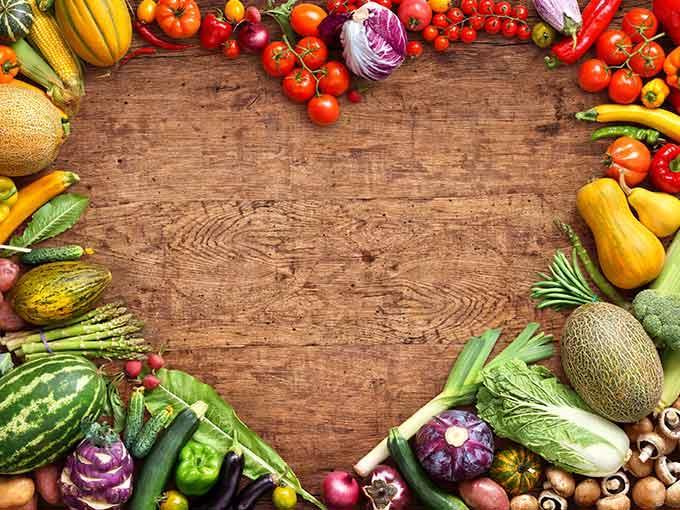 Eine Auswahl an blutdrucksenkenden Lebensmitteln liegt auf einem Holztisch, in der Mitte eine Aussparung in Herzform.