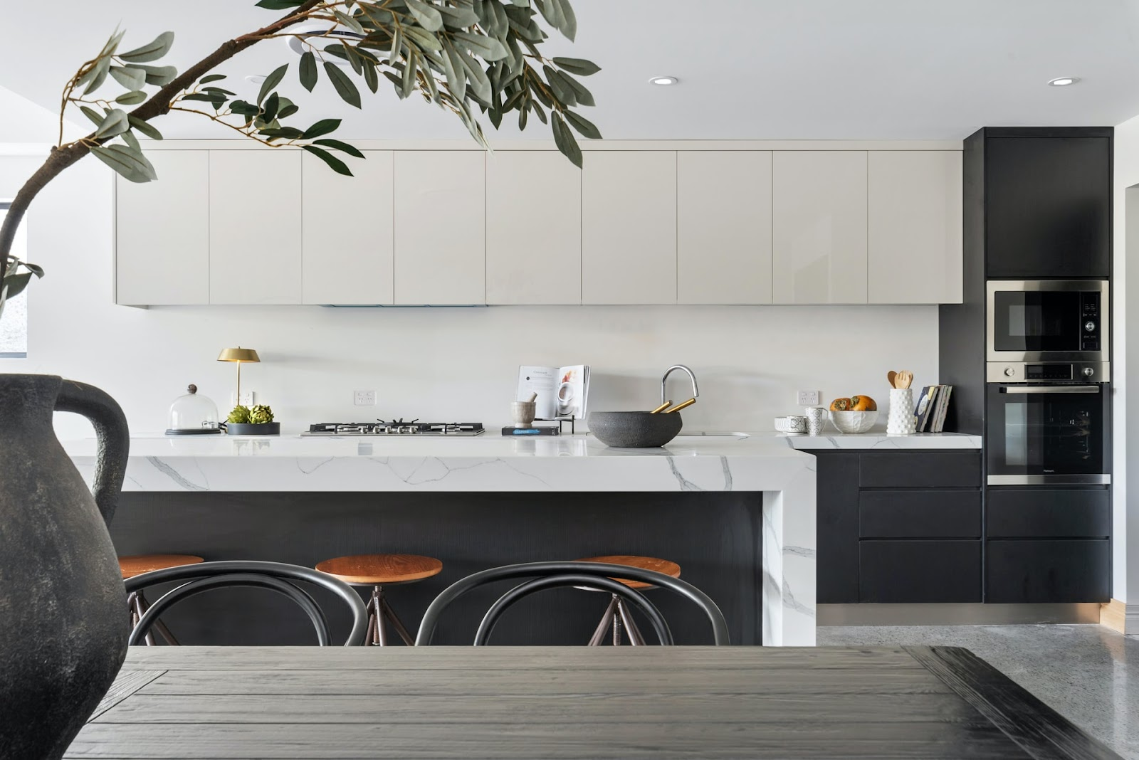 Built-in stove & smooth cabinets for a stylish minimalist kitchen design; kitchen with light grey & black cabinets