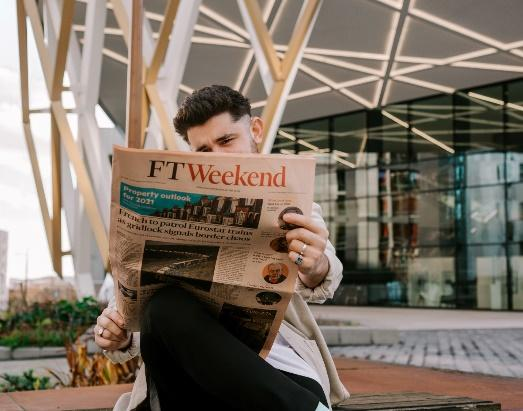 A person holding a newspaper  Description automatically generated with medium confidence