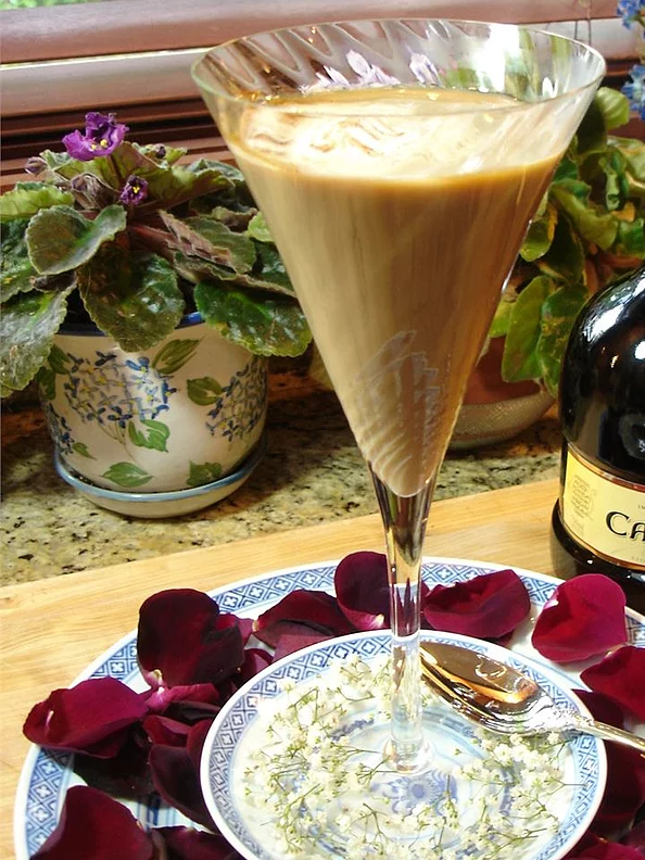An Irish coffee in a champagne glass on a plate with flower petals