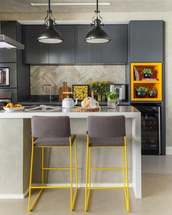 Cozinha com armários cinza e bancada da pia cinza, banca de porcelanato branca e piso em tom neutro, lâmpadas pendentes cinza escuro cadeiras amarelas com estofado cinza e nichos do armário amarelo.