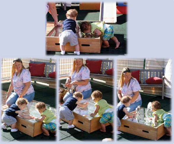 An instructor watching as two infants play with a box of mirrors