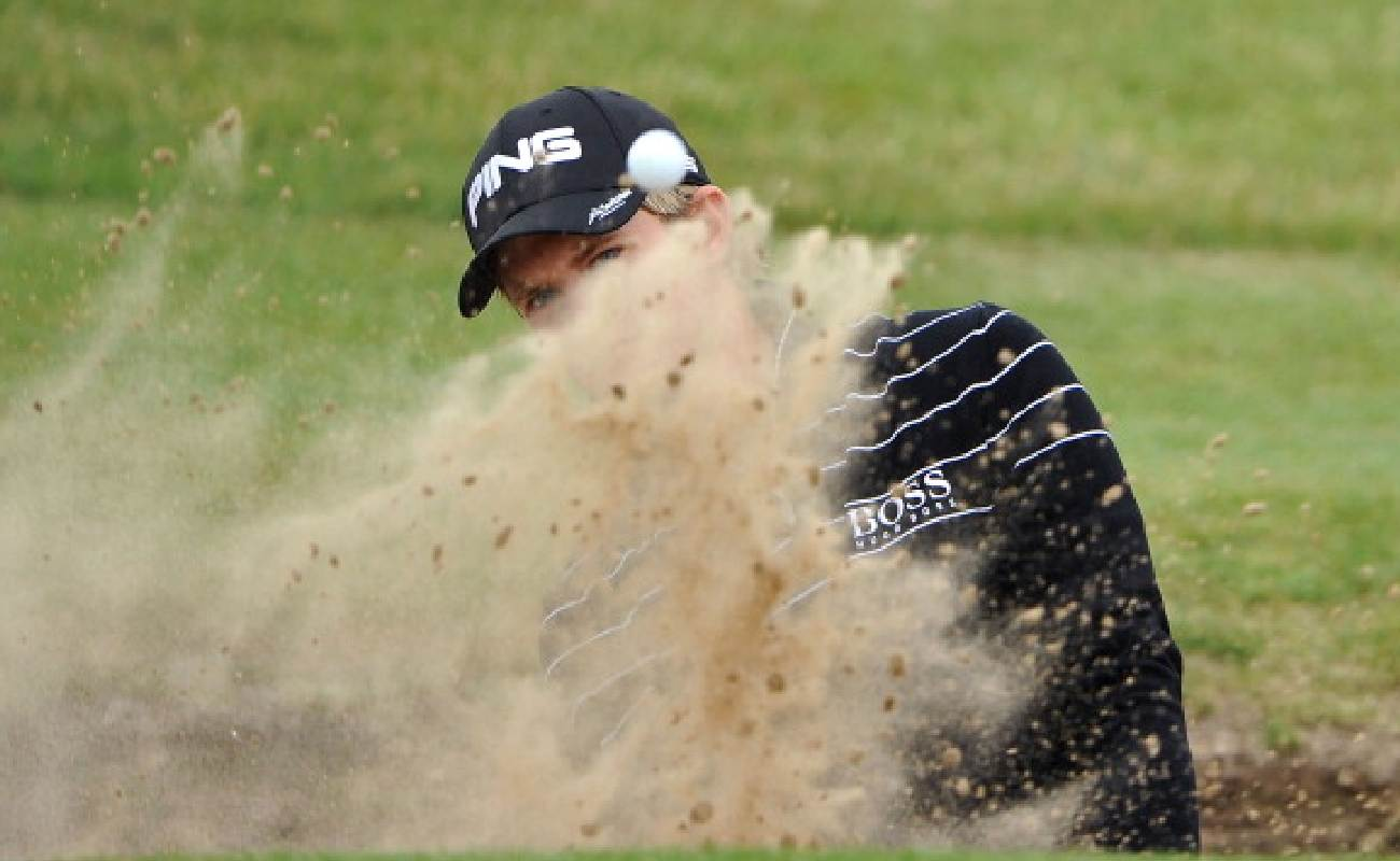 Alt: Amateur Tom Lewis of England hits from a bunker on the 6th hole during the first round of The 140th Open Championship at Royal St George's - Photo by Stuart Franklin/Getty Images