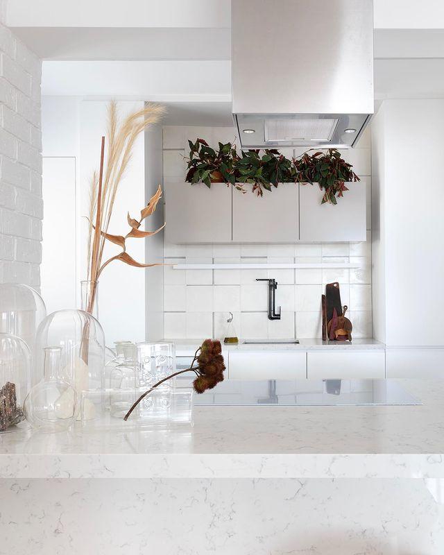 Cozinha com nuances e texturas de branco nos tijolinhos da parede, bancadas em quartzstone, ladrilho no frontão e armários