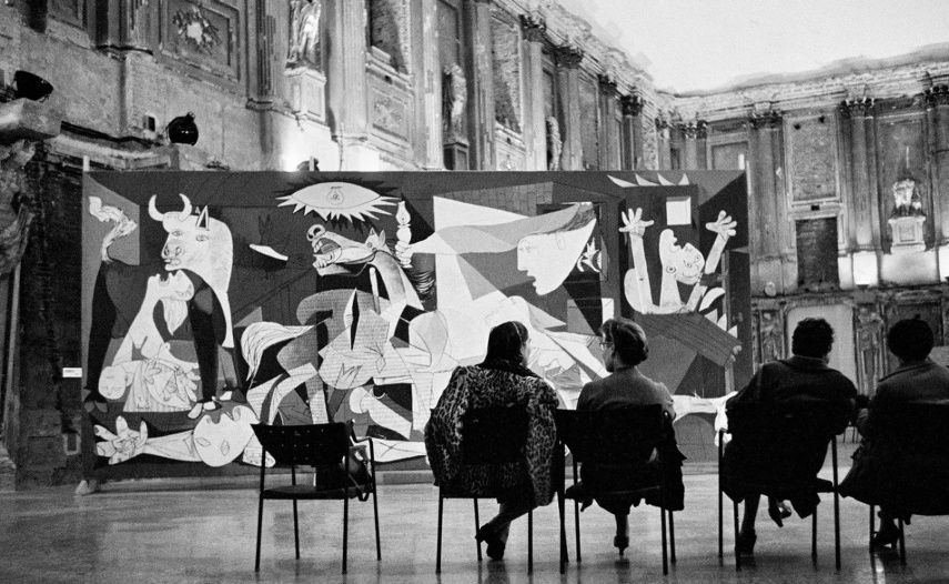 An image of a woman outside sitting in front of a Guernica copy