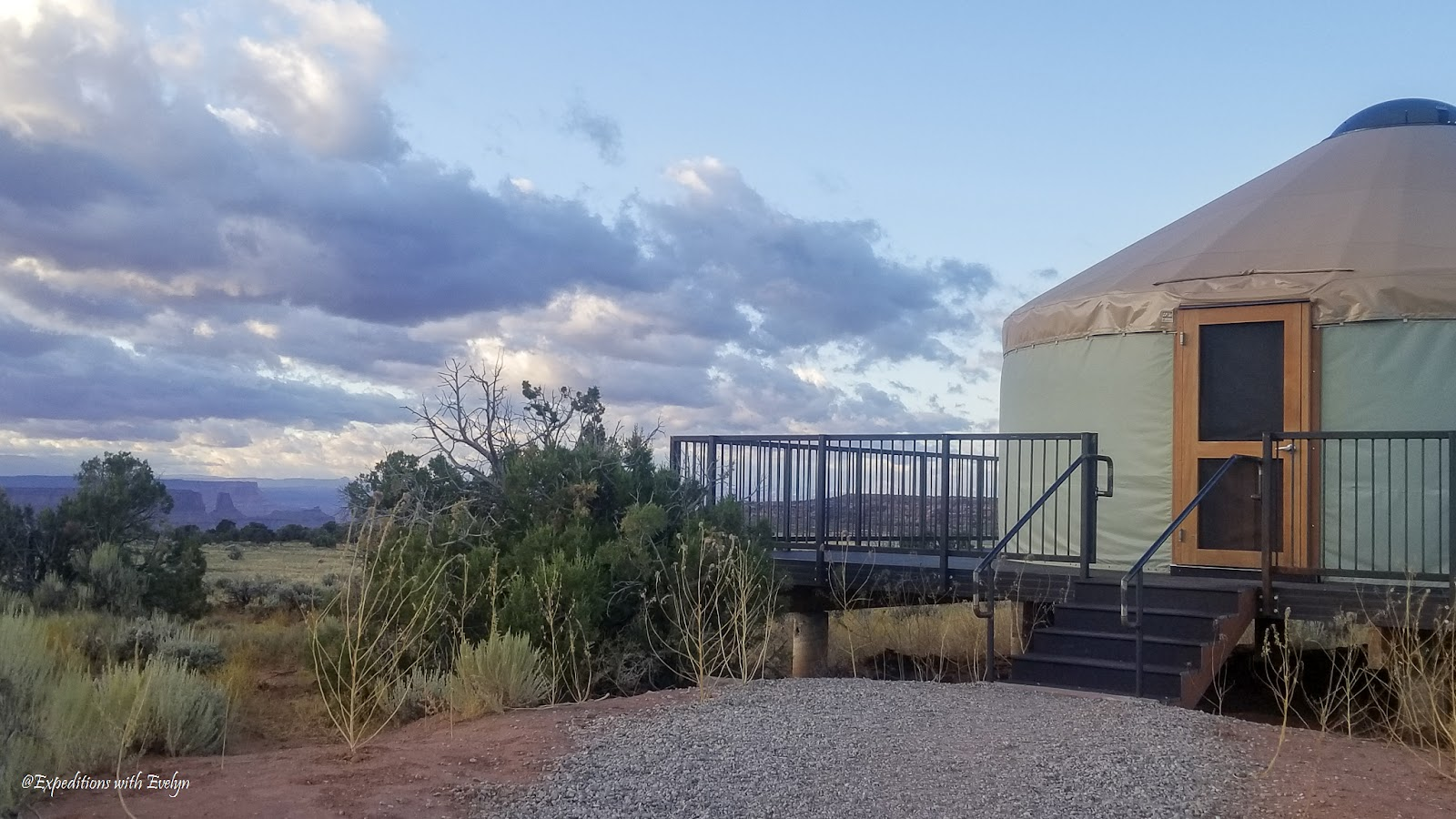 A canvas yurt with a steel porch and stairway overlooks desert plans and a canyon in the distance.