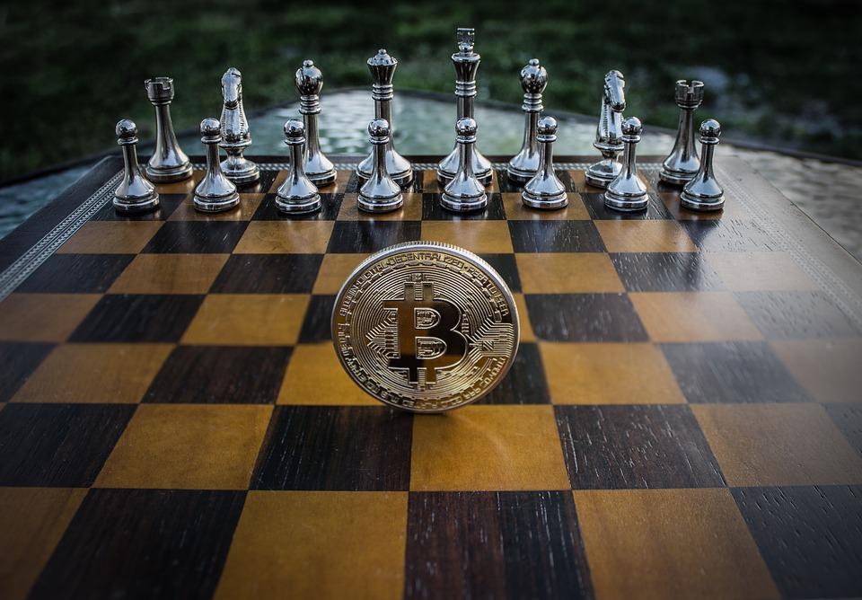 Um tabuleiro de xadrez com peças de um lado e uma moeda de Bitcoin na frente delas.