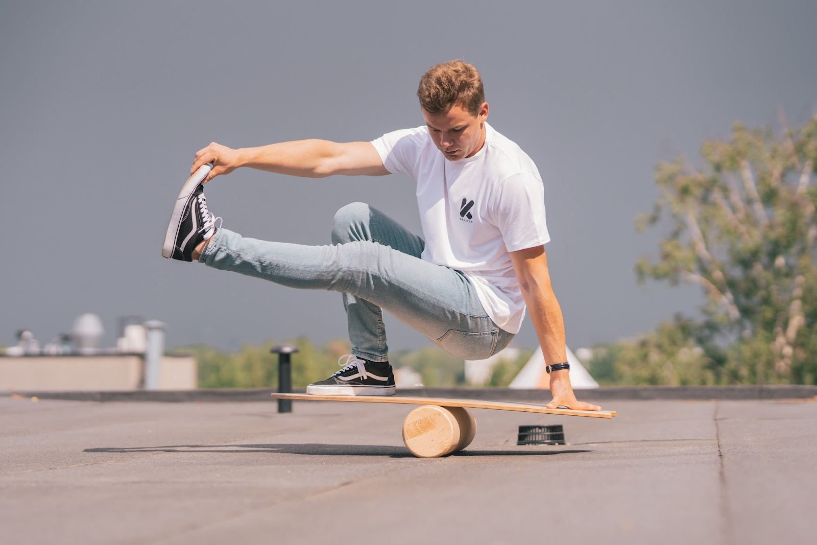 A guy balancing on a balance board on a rooftop