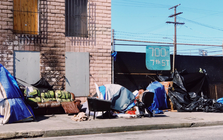Community Service with those that are homeless.  Photo of makeshift homes on a city sidewalk.