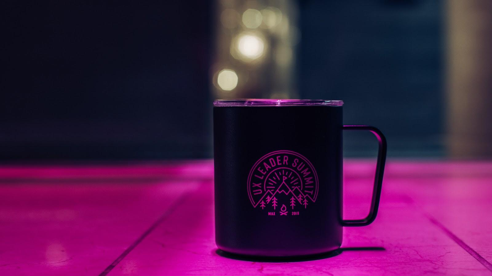 Black coffee mug with UX Leader's Summit logo on it.