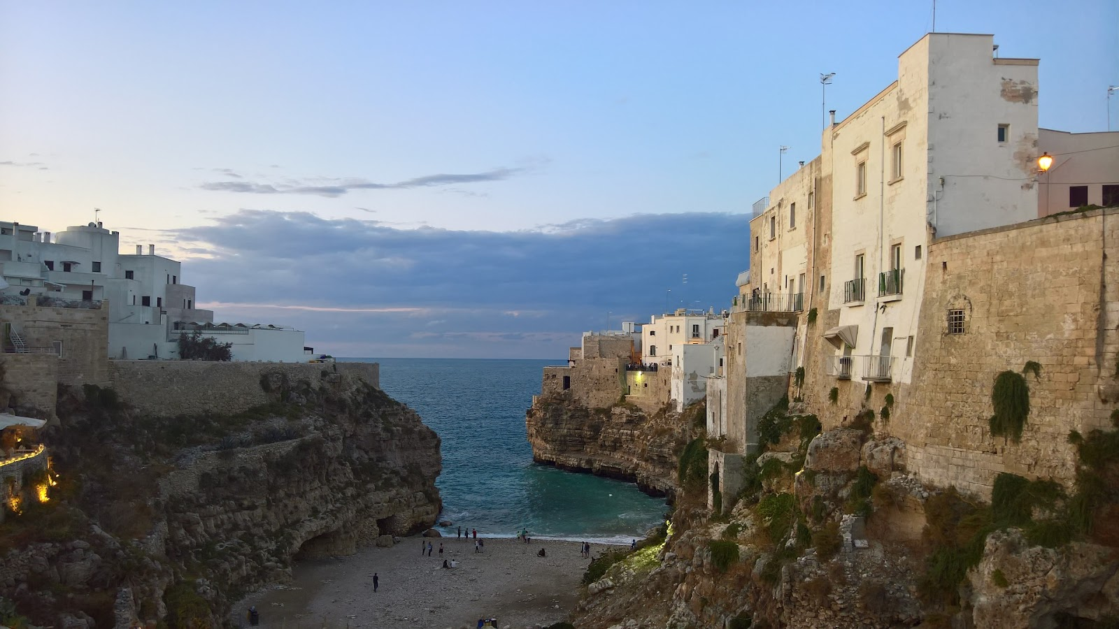 beautiful small italian sandy beach surrounded by whitewashed buildings and cliffs blue sea near bari south of italy sunset