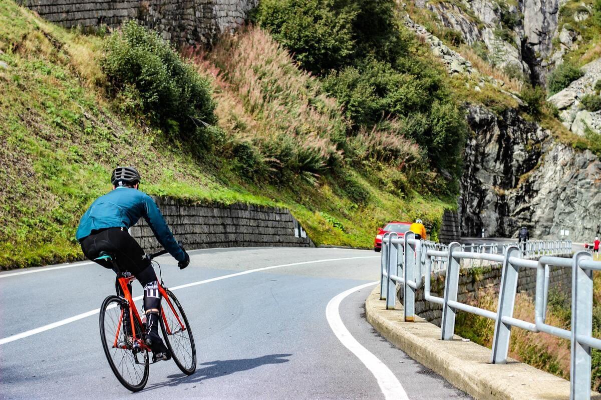 Un ciclista sportivo su una strada di montagna