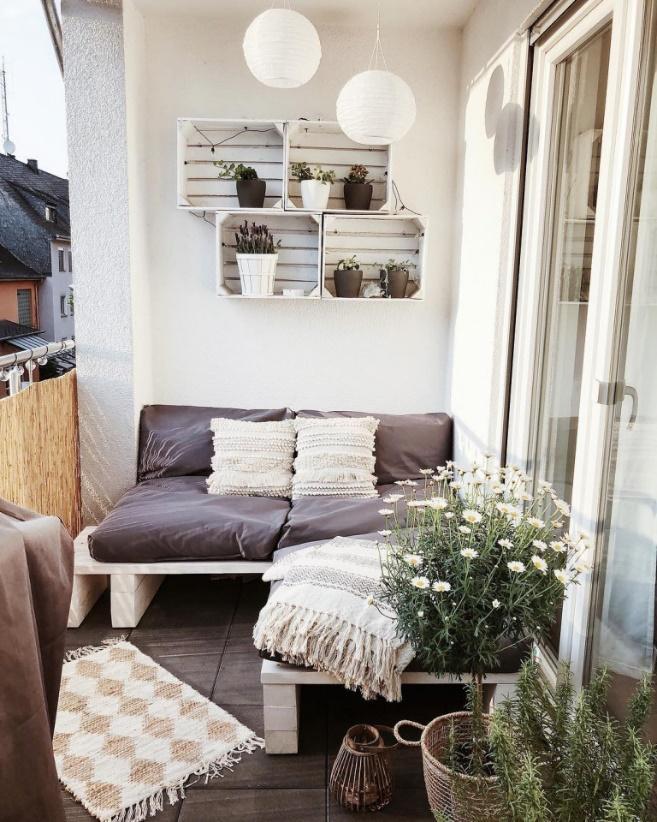 Varanda com sofá de estofado cinza escuro, paredes brancas, piso amadeirado e paletes na parede com vasos de plantas.