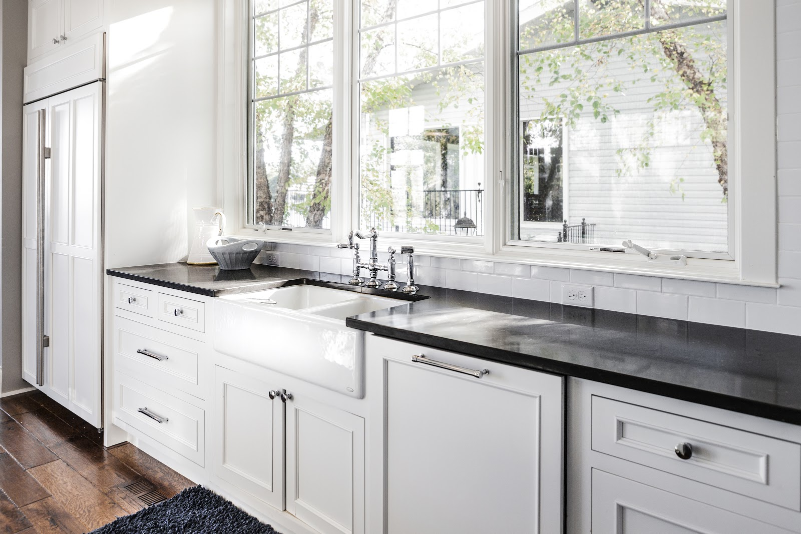 White Kitchen with black countertops, flooded by natural light from three large windows above an apron sink.