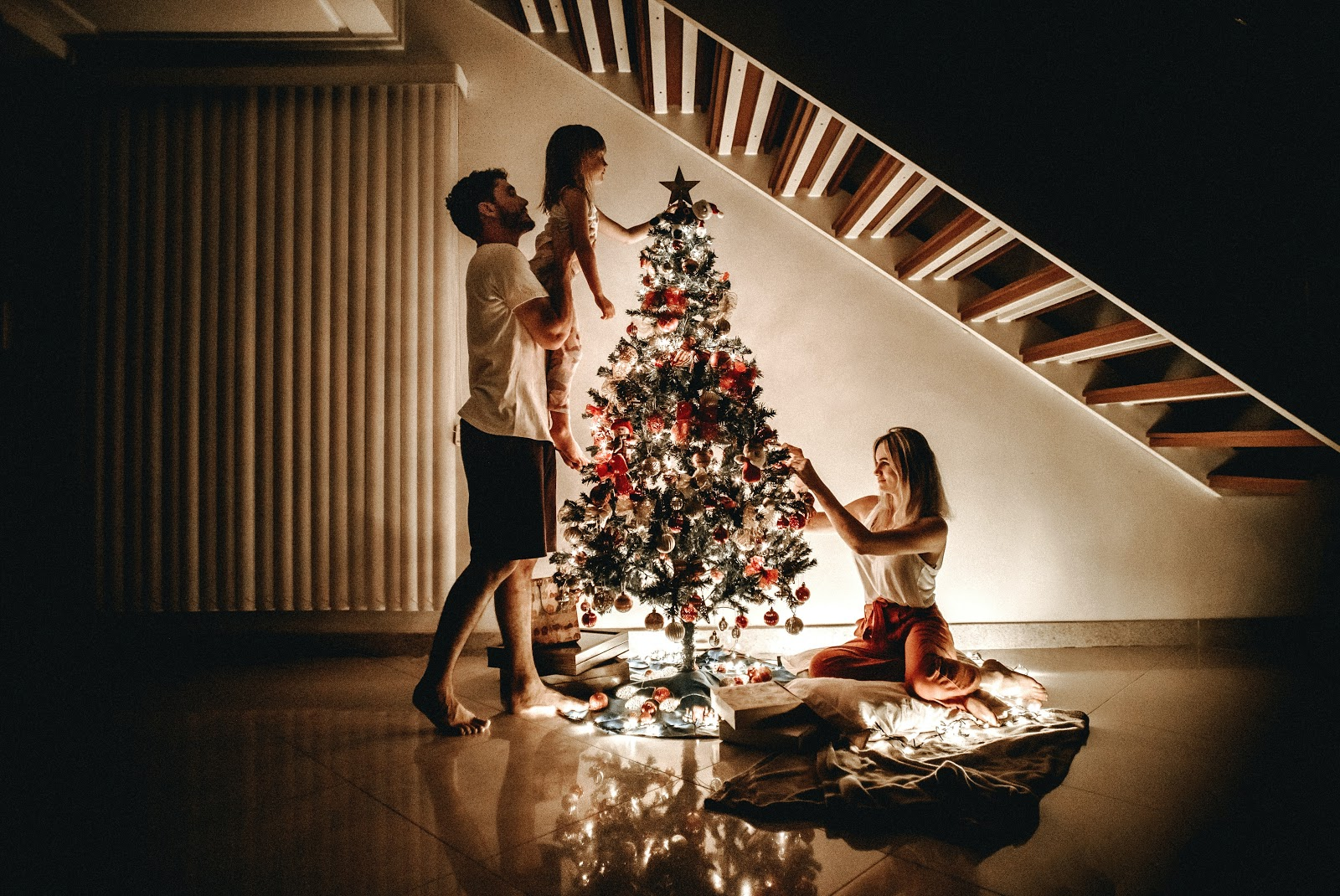 Family setting up Christmas Tree at night