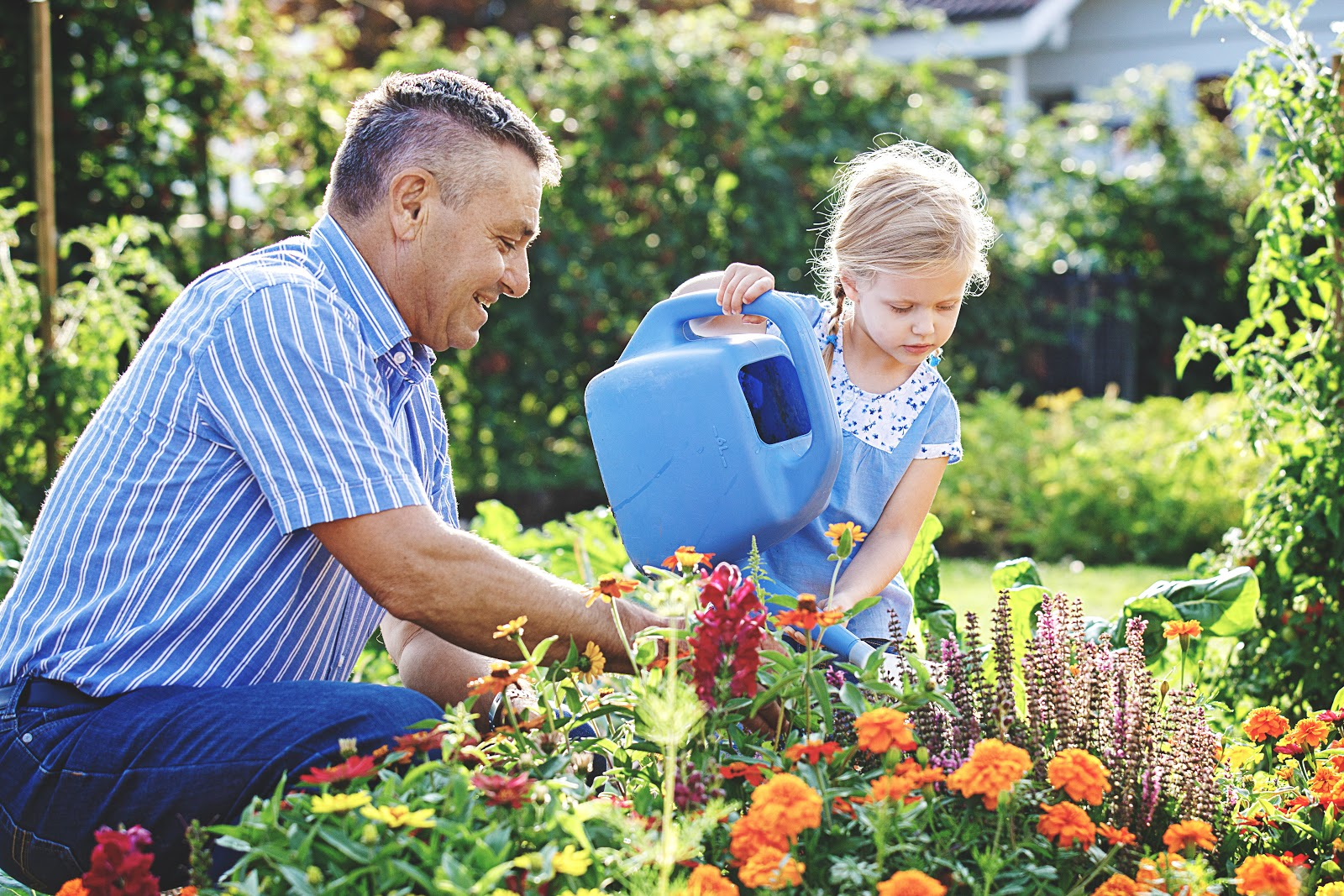 Father and daughter gardening together looking happy