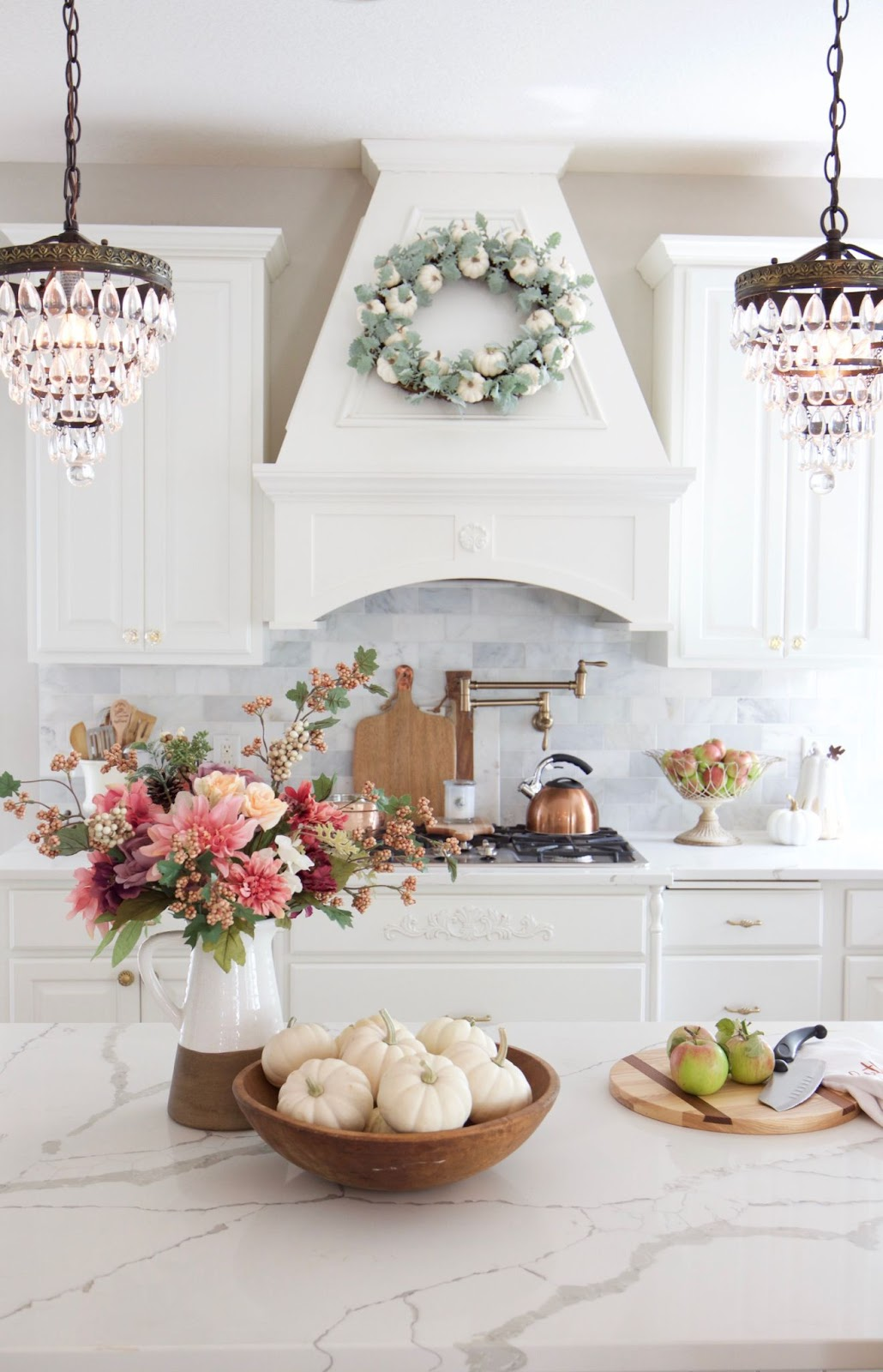 White  pumpkins and apples and fall colored flowers in kitchen.