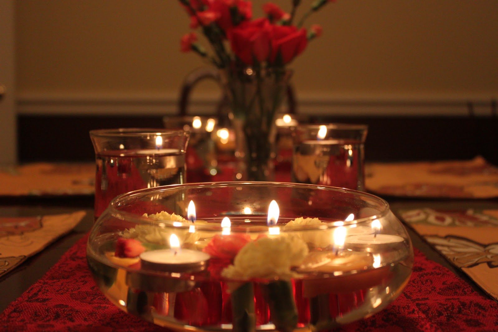 centerpiece of candles inside water with roses