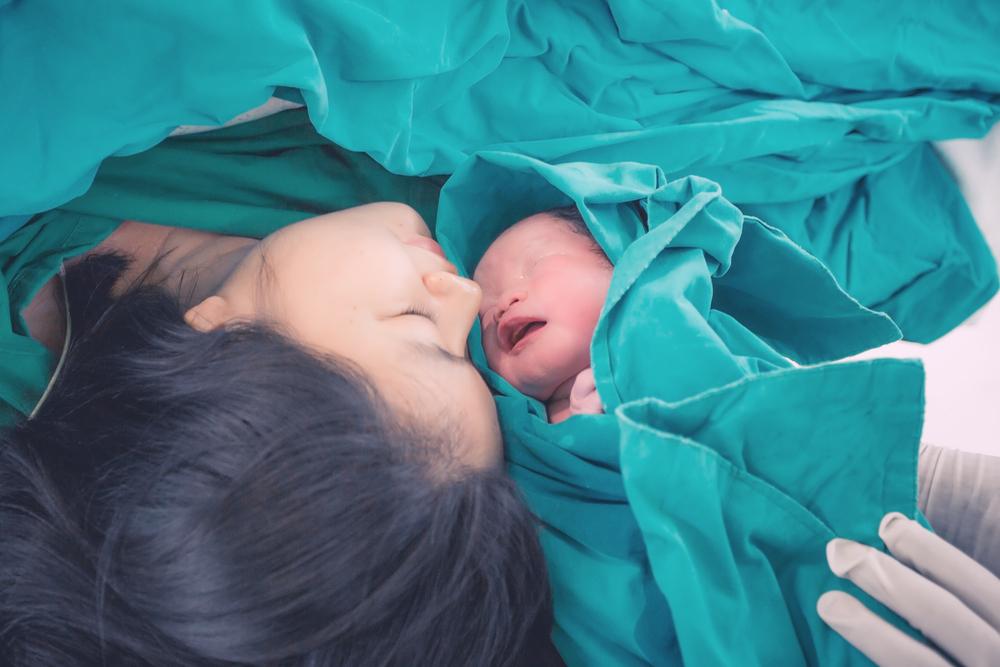 Mãe com recém-nascido enrolado em manta do hospital