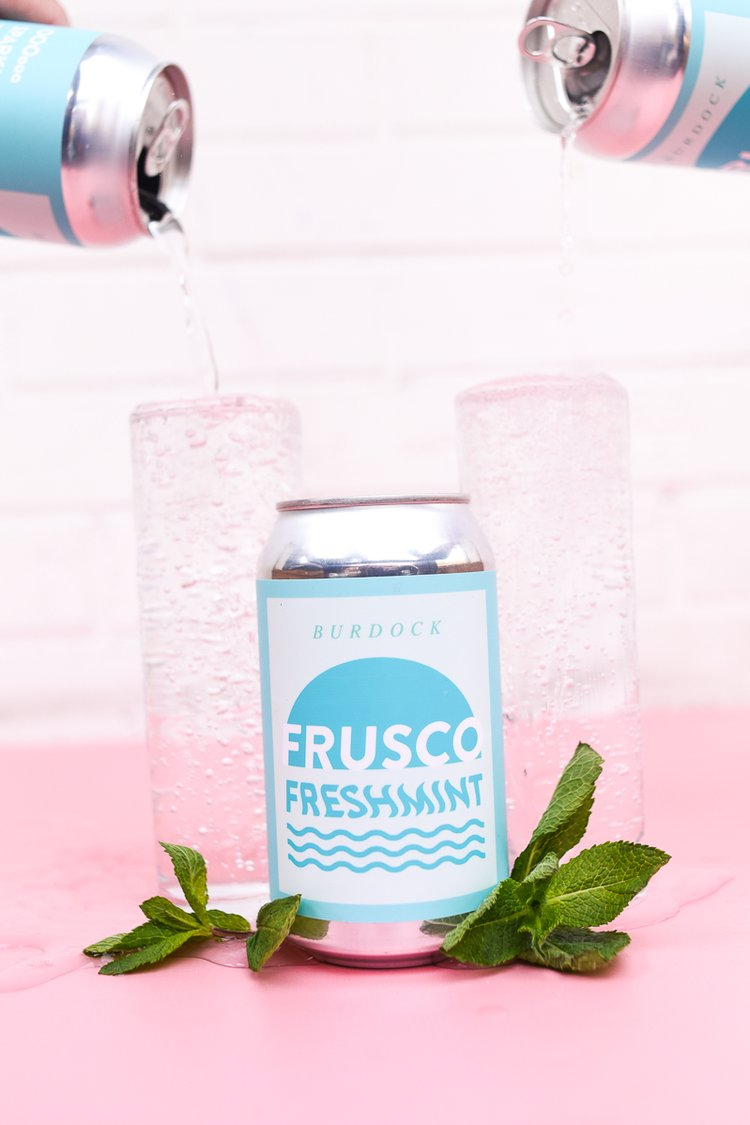 A can of Frusco Freshmint surrounded by fresh mint leaves and two glasses of the sparkling water in the background.