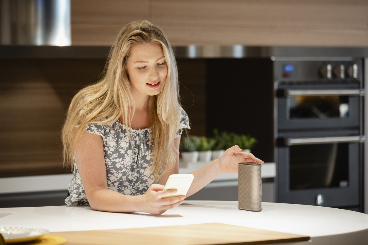 woman-connecting-smartphone-to-smart-speaker