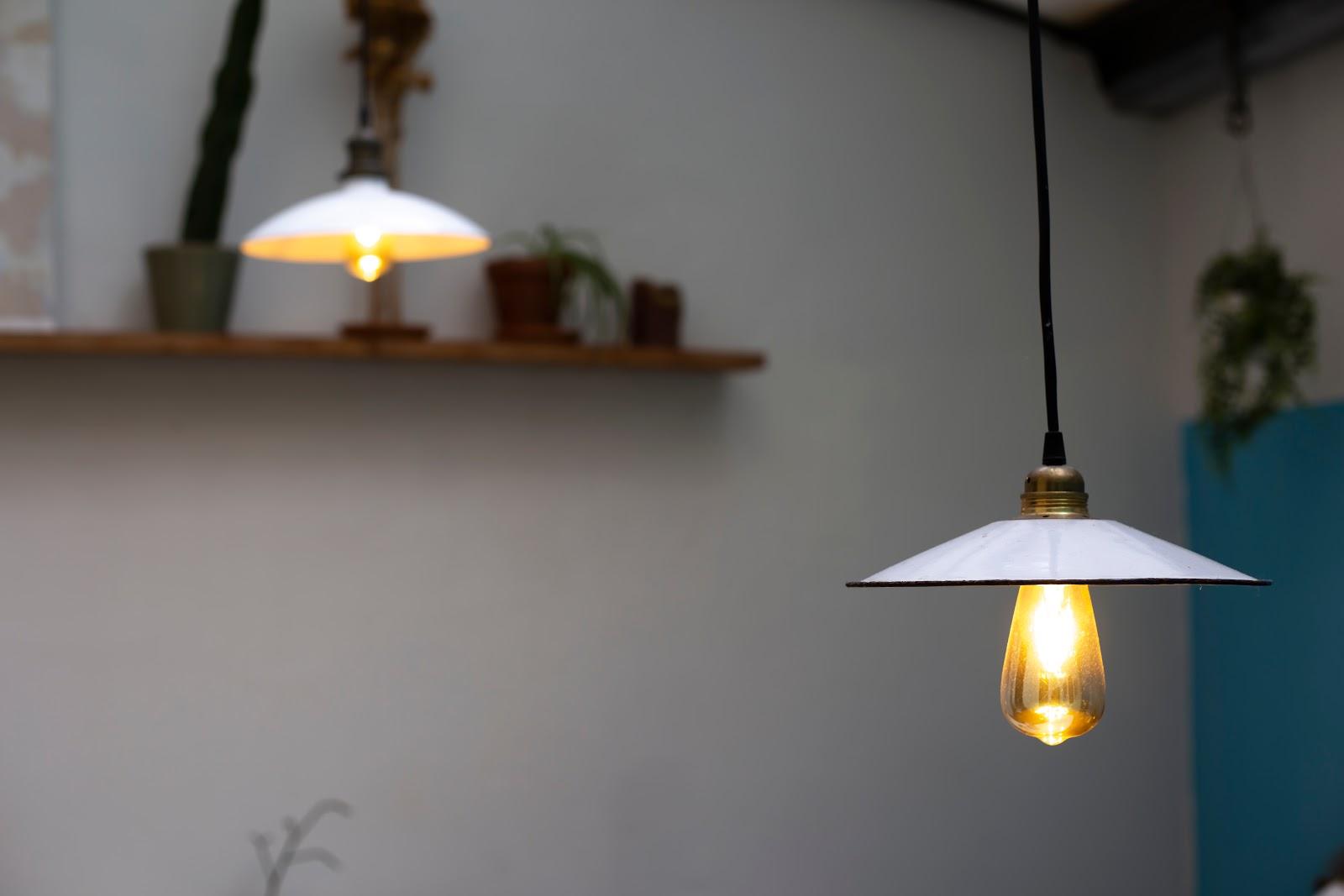 Luminária pendente com lâmpada de luz amarela.