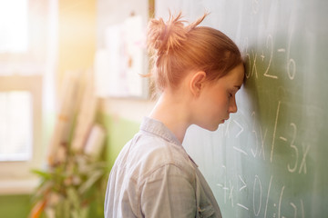 Child suffering from Math Anxiety with head against blackboard