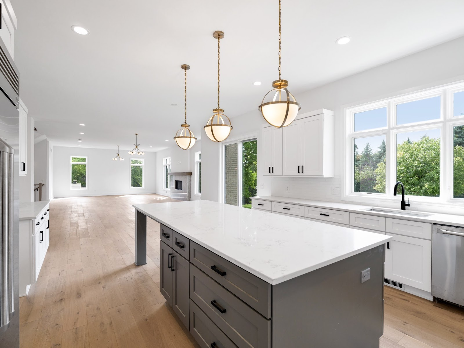 large modern kitchen with white and grey shaker cabinets and plenty of natural lighting. matte black hardware and faucet tie together the design