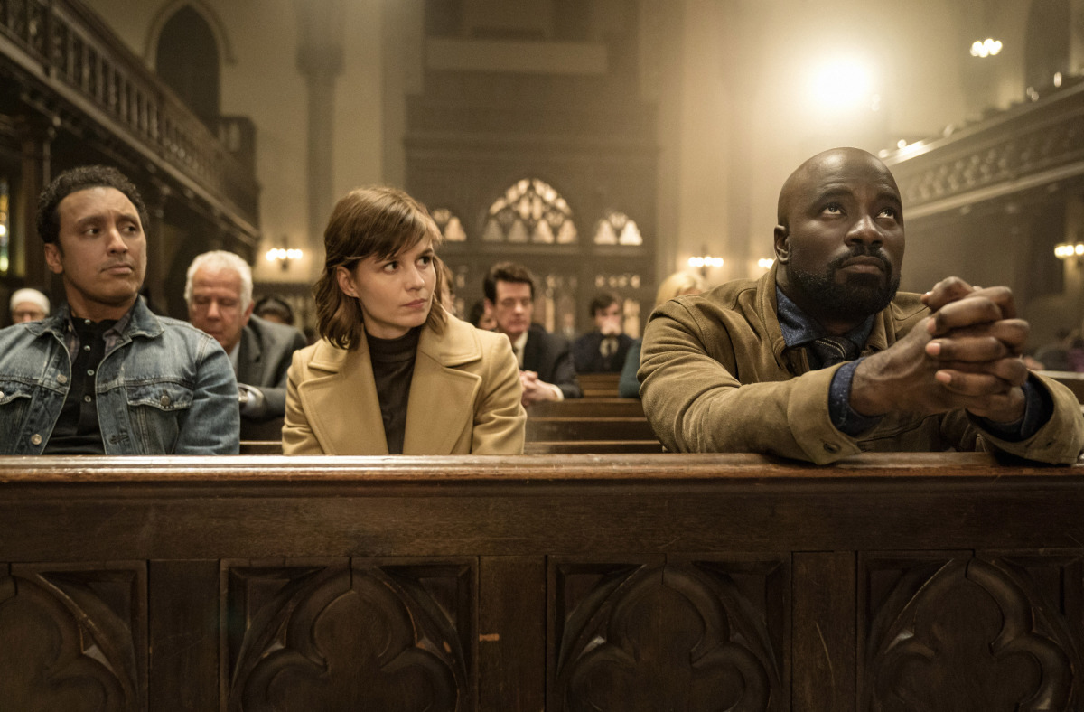 Aasif Mandvi, Katja Herbers, and Mike Colter as Ben Shakir, Kristen Bouchard, and David Acosta in Evil (2019–). Ben, Kristen and David are sitting on a pew in a busy church. David has his hands clasped on the bench in front of them, looking up to the ceiling, as Ben and Kristen watch him curiously.