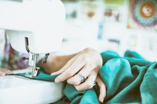 Immagine che contiene macchina da cucire, persona, apparecchio, interniDescrizione generata automaticamente